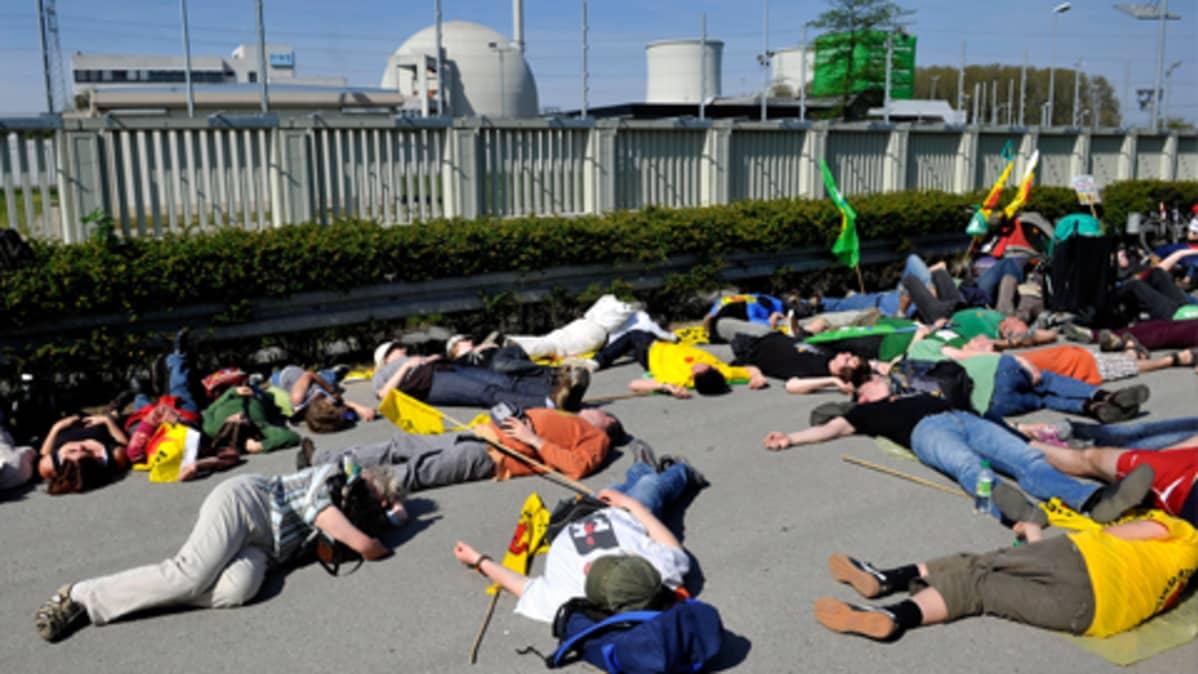 Ydinvoiman vastustajat makaavat tiellä Biblisin ydinvoimalan luona mielenilmauksena.