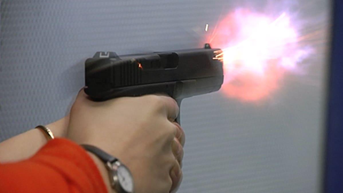 Mies ampuu käsiaseella