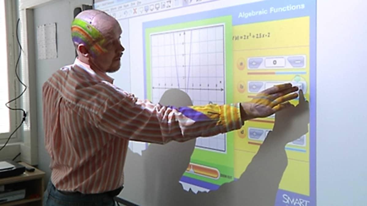 Opettaja käyttää kosketusnäytöllä toimivaa älytaulua.