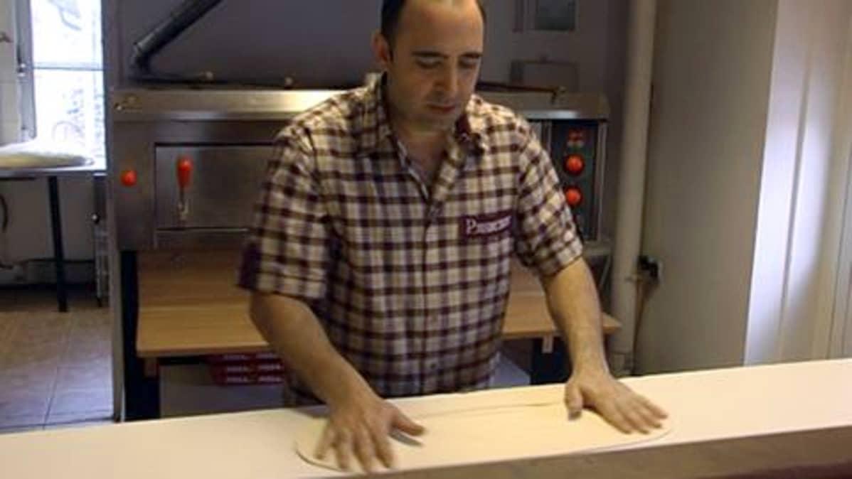 Ravintoloitsija Erkan Uzun pyöräyttää pizzapohjan