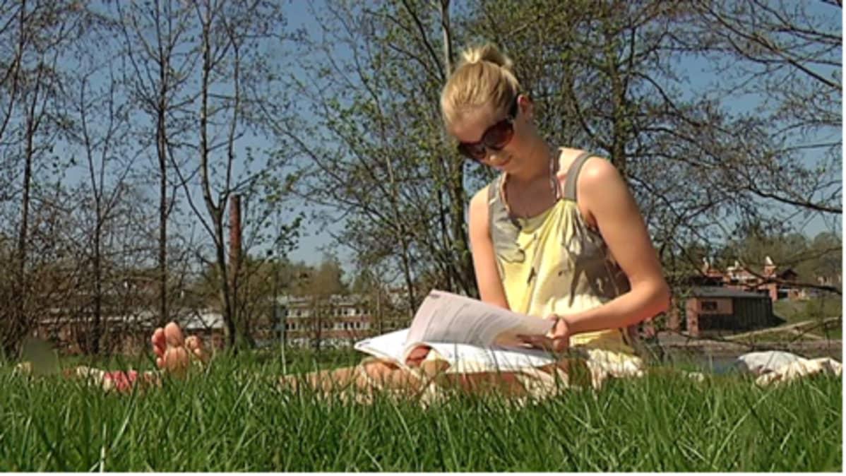Nainen lukee kirjaa hellesäässä.