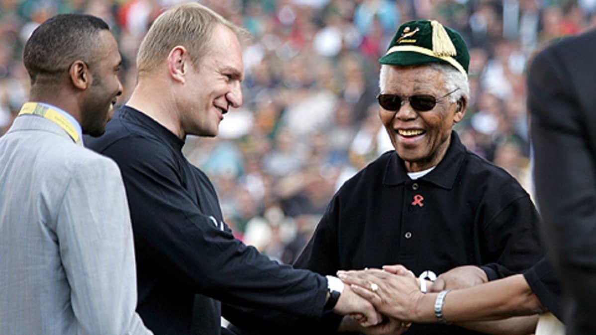 Rugby-tähti Francois Pienaar kättelee Etelä-Afrikan entistä presidenttiä Nelson Mandelaa Johannesburgissa rugbystadionilla vuonna 1995. Mandelalla Springbok-joukkueen hattu.