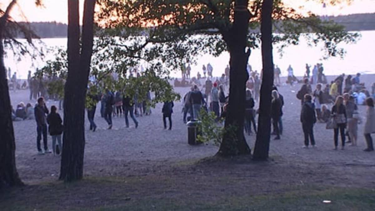 Nuoria rannalla juhlimassa koulujen päättymistä auringon laskiessa