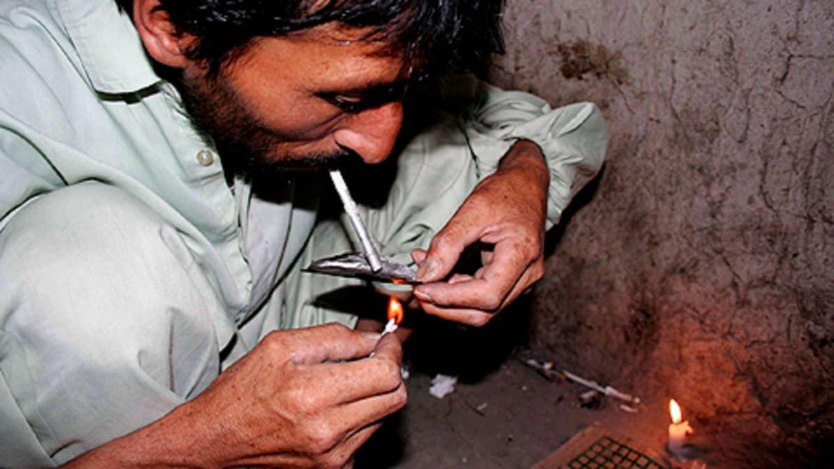 Afgaanimies polttaa heroiinia