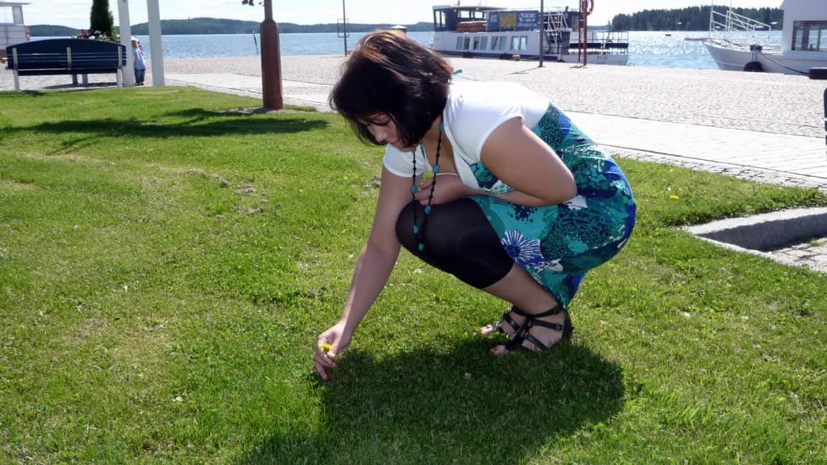 Saara Hanhela poimii kukkaa juhannustaikoja varten.
