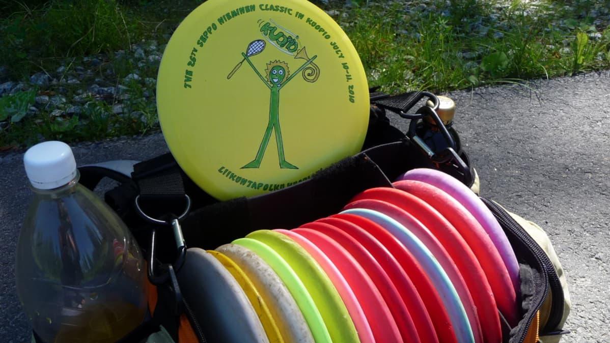 Frisbeegolfharrastajan kassista löytyy erilaisia kiekkoja riittämiin.