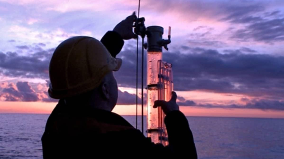 Mies kerää vesinäytteitä avomerellä ilta-auringon laskiessa turkooseissa väreissä.