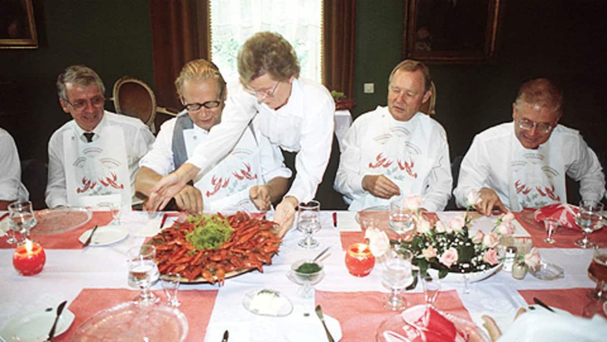 Ihmisiä rapujuhlien ruokapöydässä