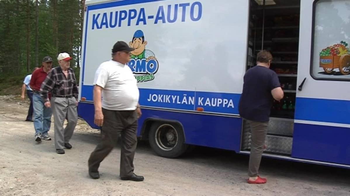 Miehet kävelevät kauppa-autolle