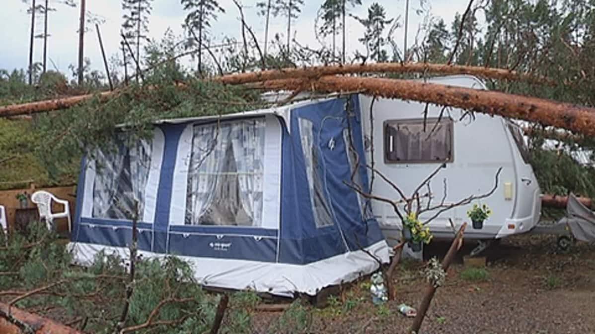 Myrskytuulen kaatamia puita asuntovaunun päällä