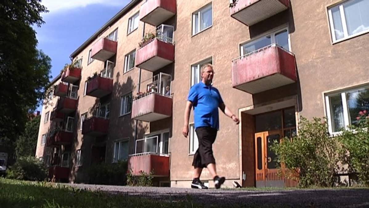 Mies kävelee kerrostalon edessä.