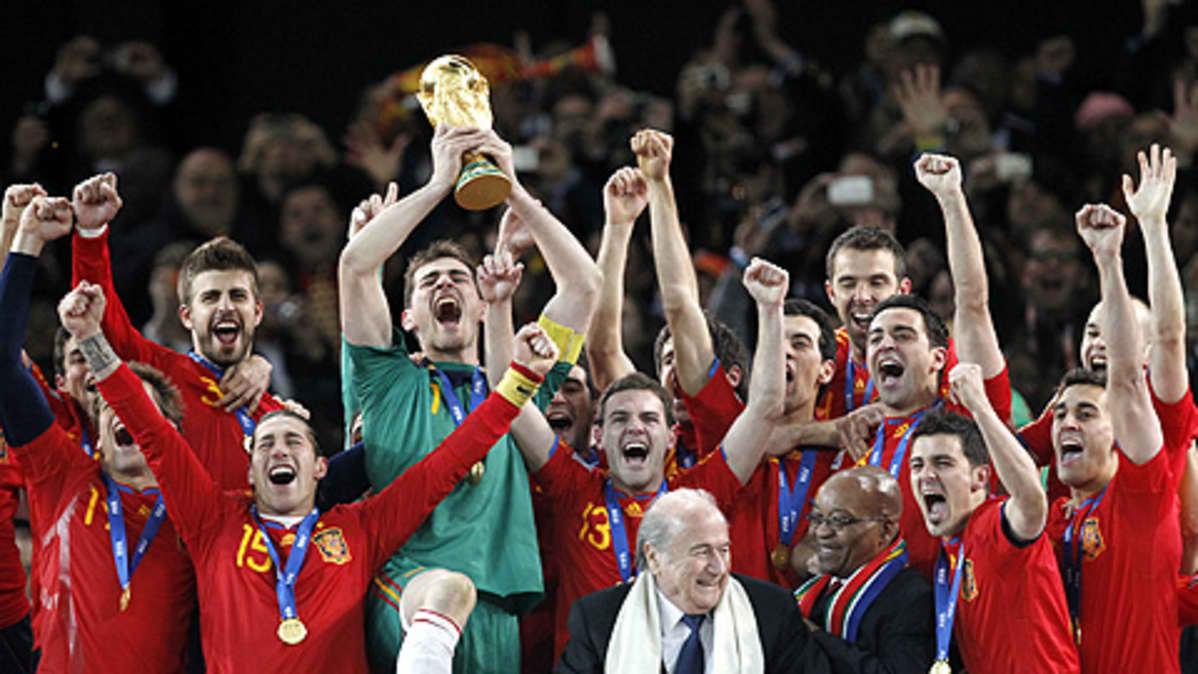 Espanjan maalivahti Iker Casillas nostaa pokaalin ilmaan joukkueen voitettua jalkapallon MM-kisojen finaalin Etelä-Afrikassa. Joukkue riemuitsee vierellä.