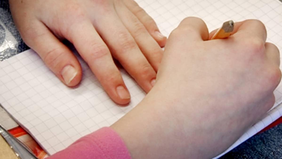 Lapsi kirjoittaa vihkoon alakoulun oppitunnilla.