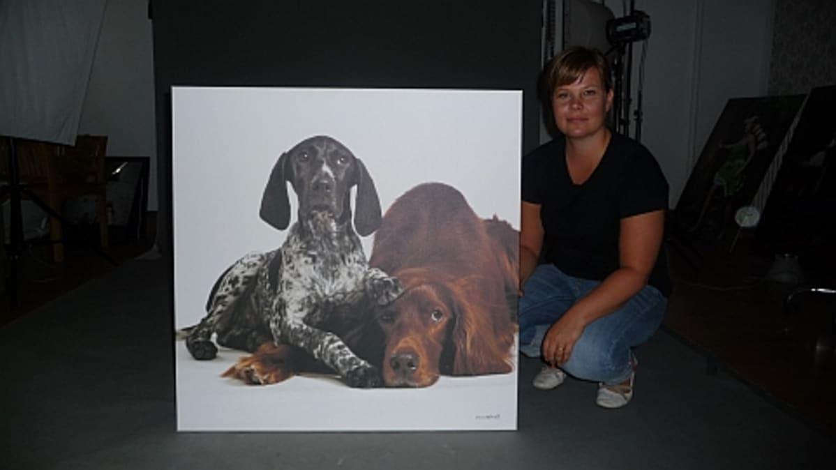 Valokuvaaja Johanna Sjövall on kyykyssä taulun vieressä.
