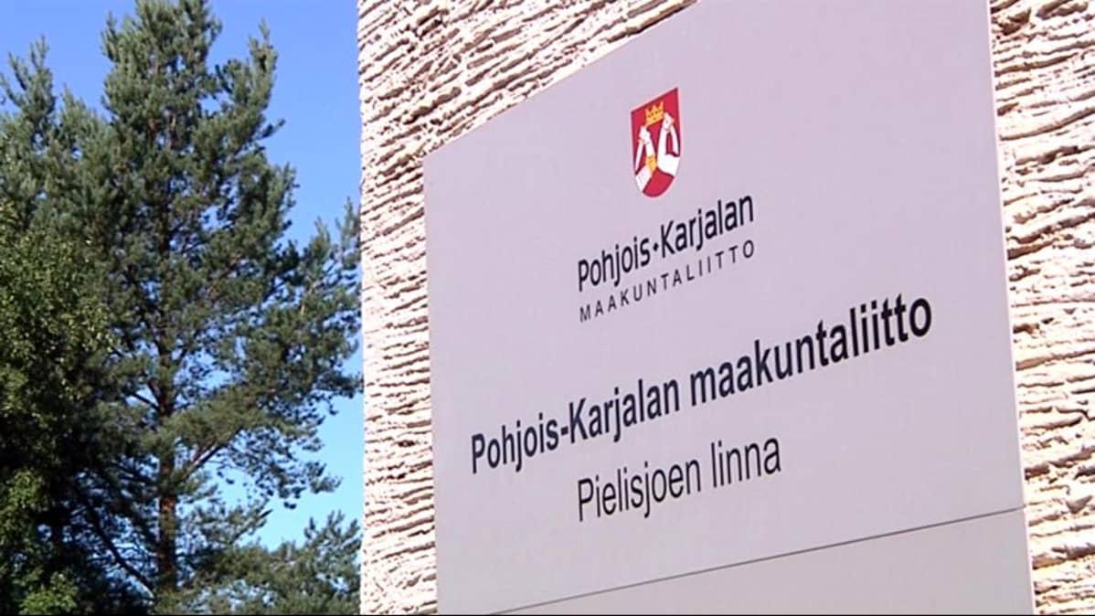 Pohjois-Karjalan Maakuntaliiton kyltti Pielisjoen linnan seinässä.