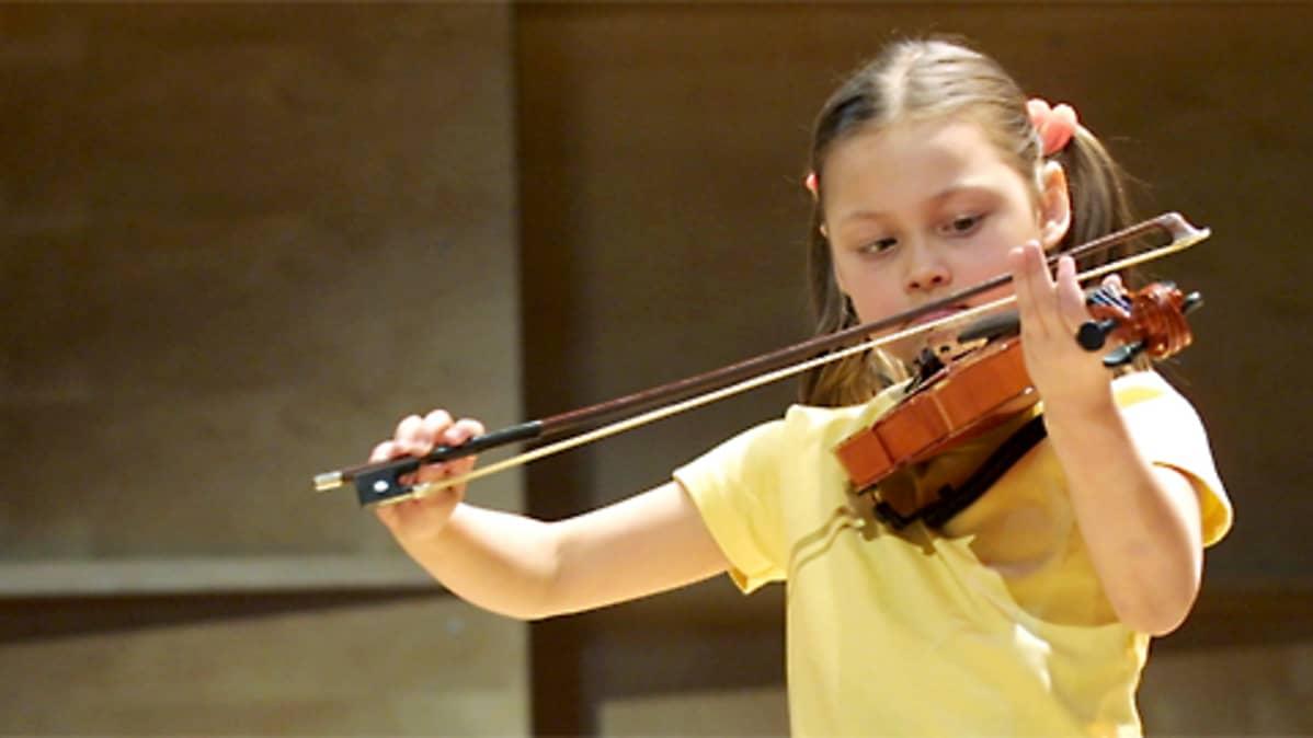Pieni tyttö soittaa viulua.