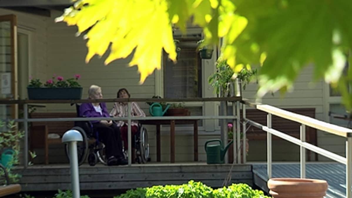Kaksi ikäihmistä hoitokodin edustalla pyörätuoleissaan.