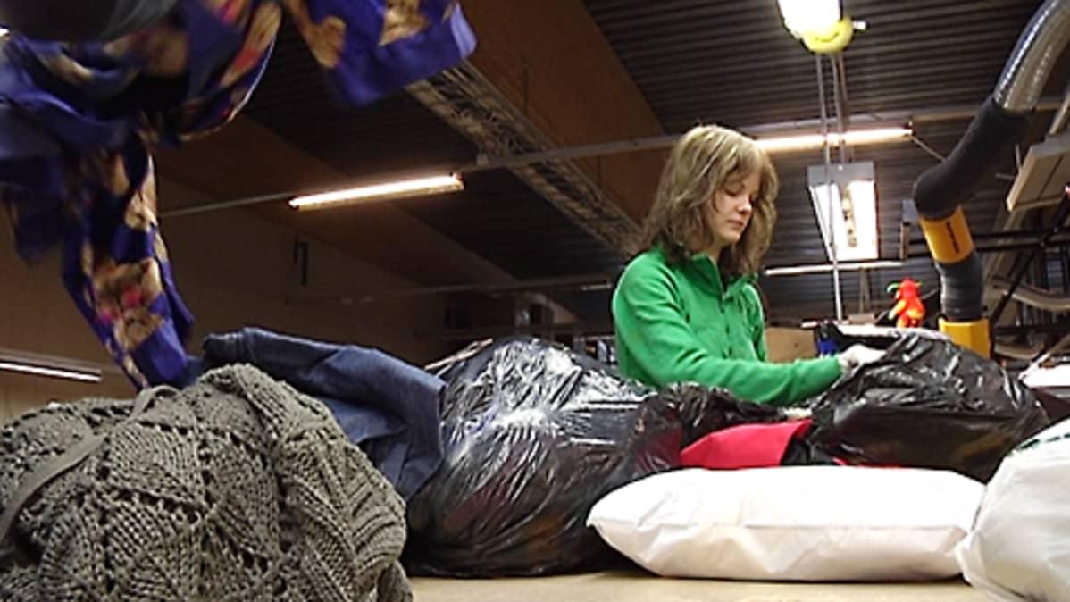 Nainen lajittelee vaatteita.