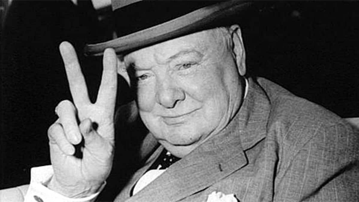Iso-Britannian pääministeri Winston Churchill näyttää voitonmerkkiä