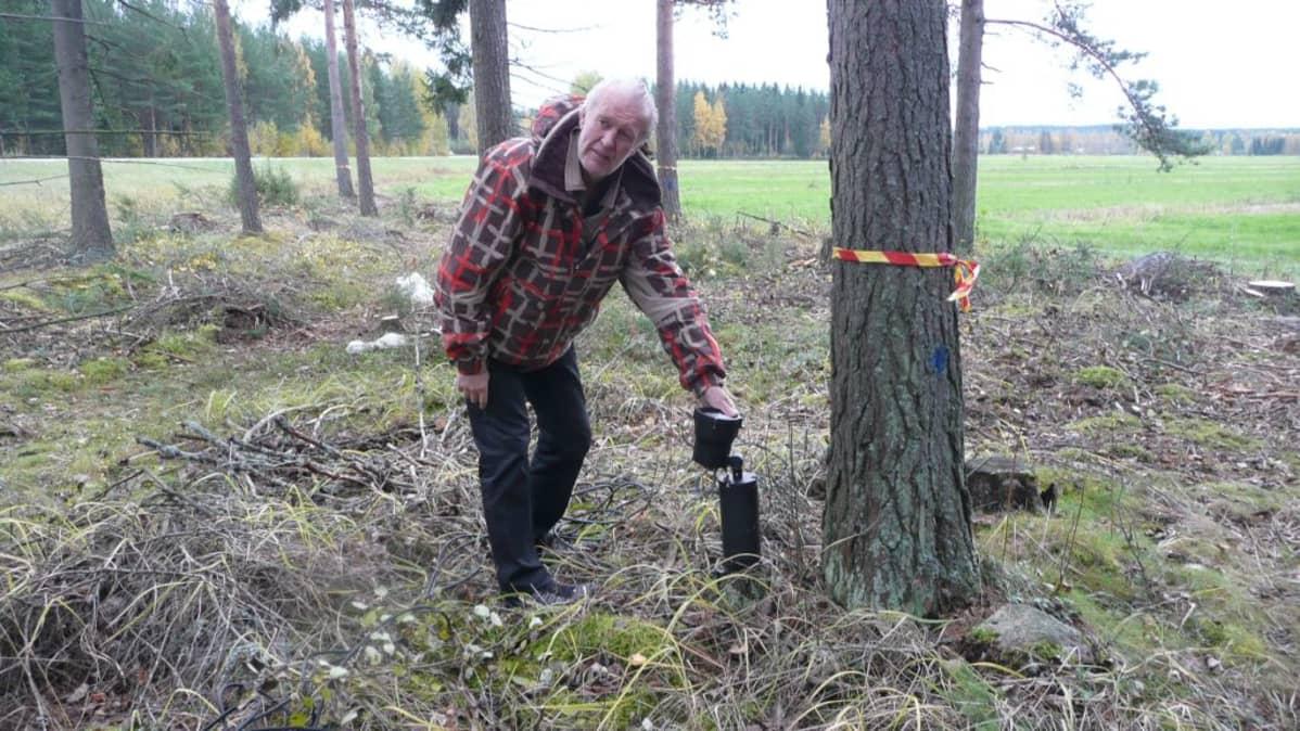 Ekku Peltomäki suunnittelee valonheittimen paikkaa metsässä.