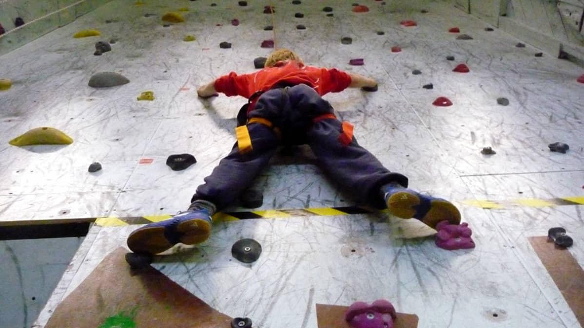 Nuori poika kiipeilyseinällä.