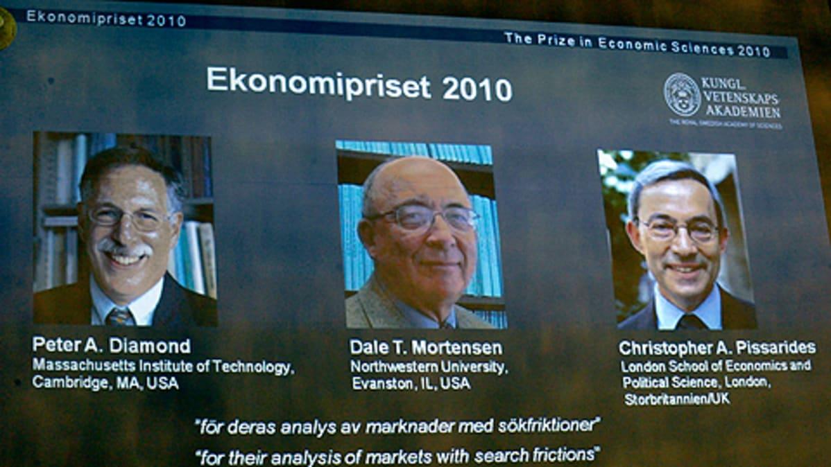 Talouden Nobel-palkinnon voittajien kuvat heijastettuna kankaalle palkinnon julkistamistilaisuudessa.