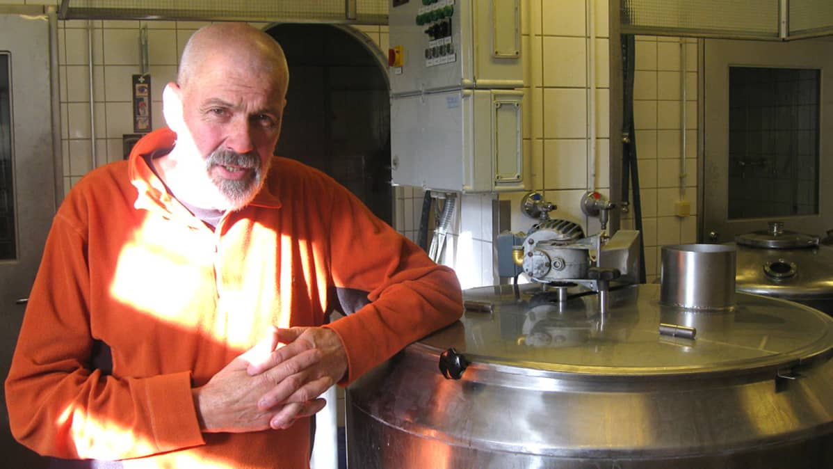 Mies ja suuria metallisia olutsammioita