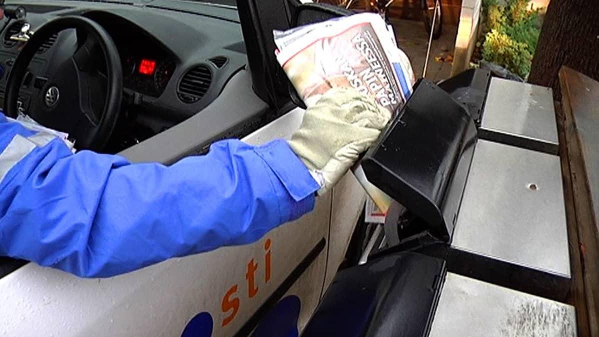 Postia jaetaan autosta laatikkoon.