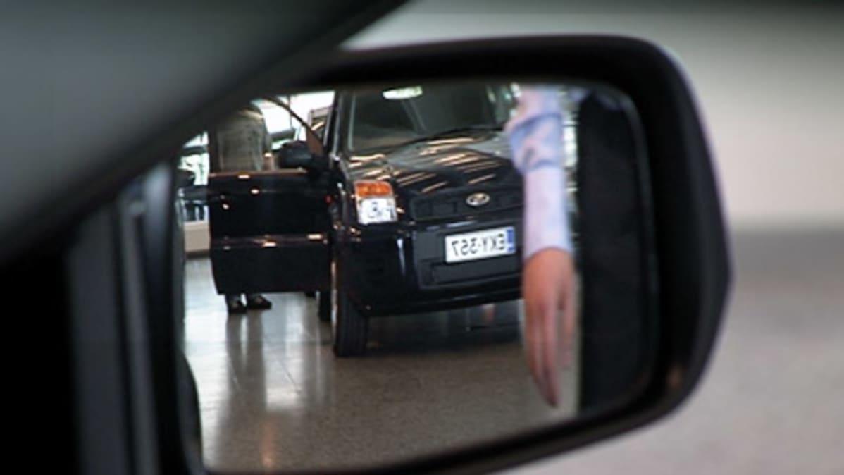 Autokauppa heijastuu auton sivupeilistä.