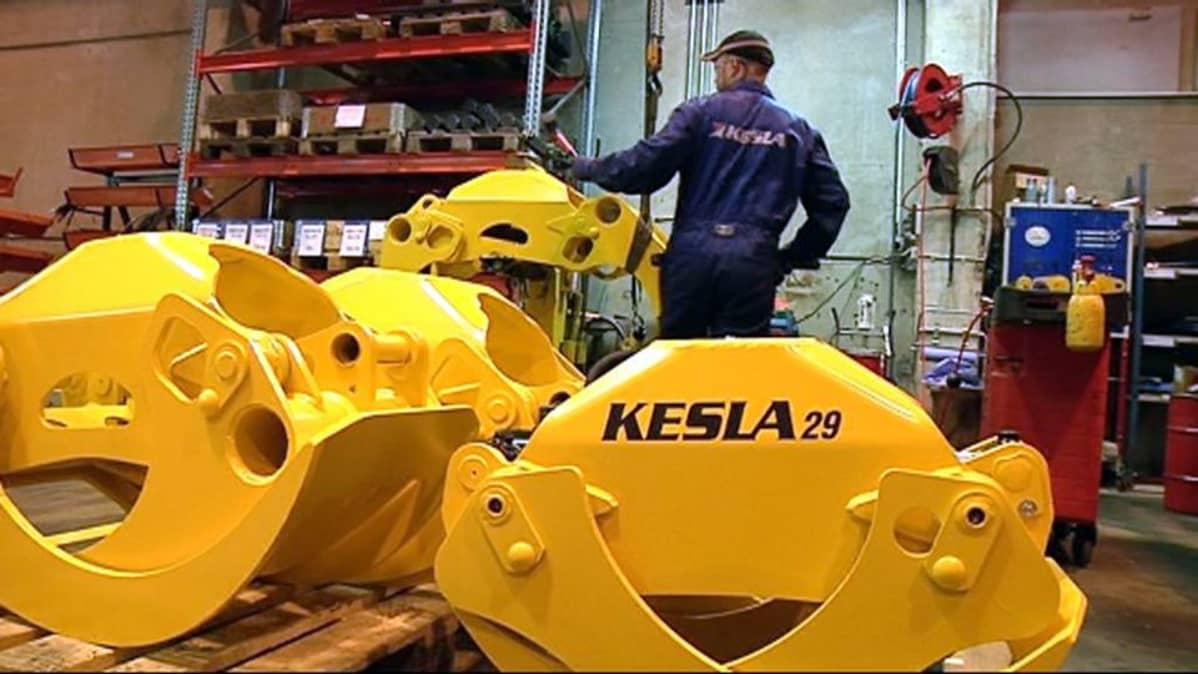 Keltaisia koneen osia ja työntekijä Keslan tehtaalla.