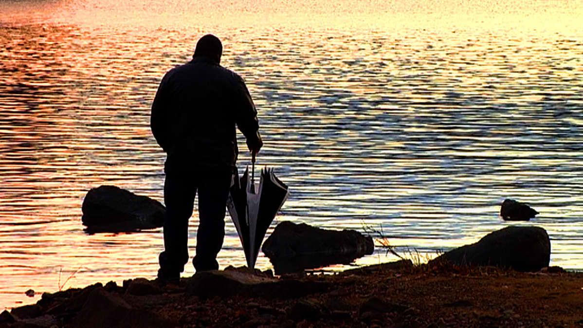 Mies rannalla auringonlaskussa.