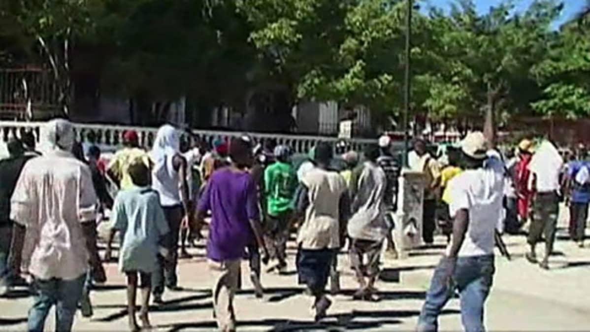 Haitilaiset juoksevat kohti YK:n kuljetusautoa