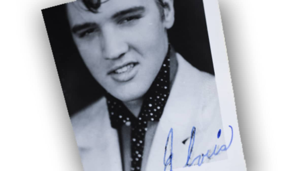 Elviksen valokuva ja sinisellä kuulakärkikynällä kirjoitettu nimikirjoitus.