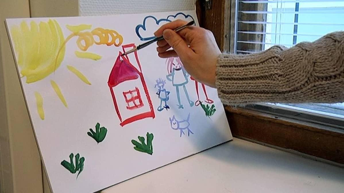 Vesiväripiirroksessa sivellin maalaa perheen ja talon.