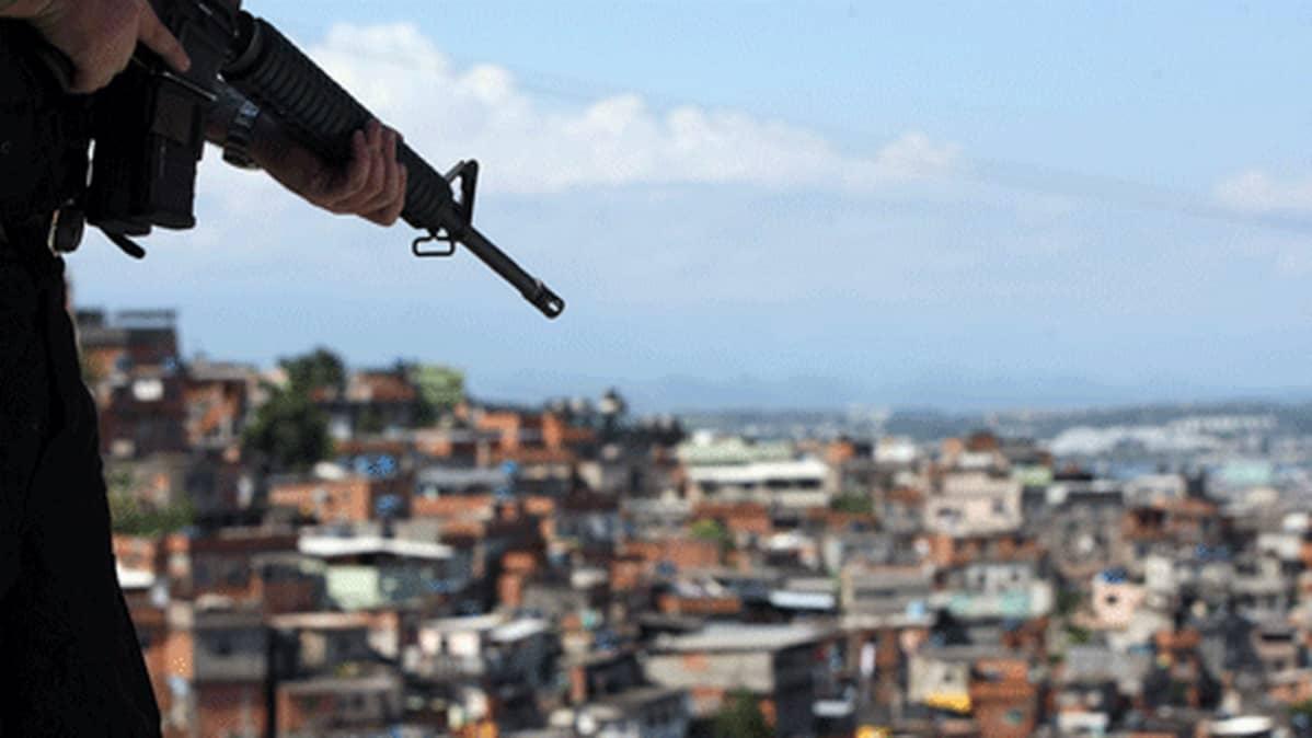 Sotilaan aseen piippu osoittaa kohti slummikaupunginosaa Rio de Janeirossa.