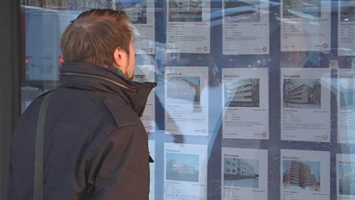 Mies katselee asuntoilmoituksia liikkeen näyteikkunasta.