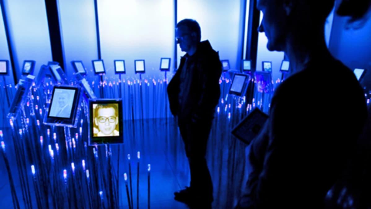 Sinisävyisessä huoneessa ihmiset katselevat Liu Xiaobon ja muiden aikaisempien rauhanpalkintojen saaneiden kuvia, jotka ovat jaluistoilla sähkökynttilöiden välissä.