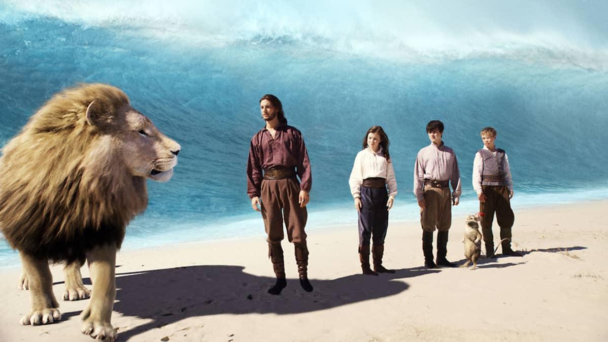 Leijonan takaa nousee jättimäinen aalto. Rannalla on yksi aikuinen mies ja kolme lasta.