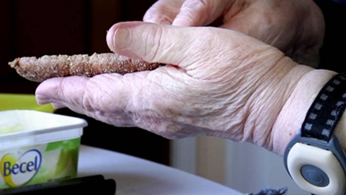 Vanhus levittää margariinia ruisleivän päälle.