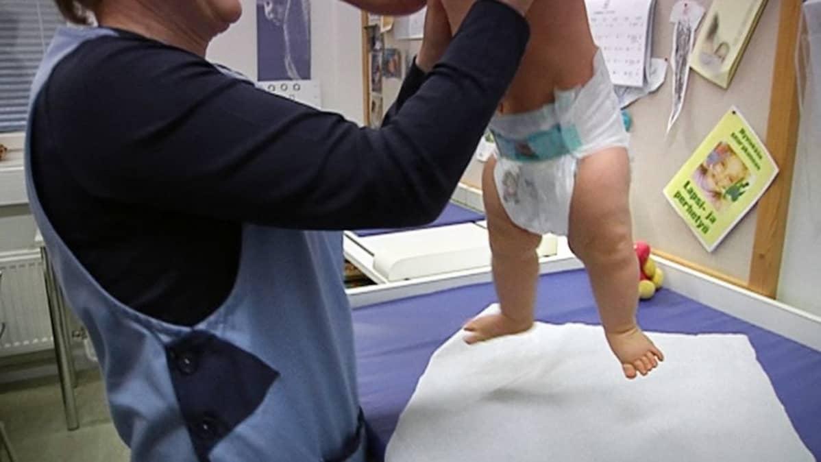 Terveydenhoitaja tutkii vauvaa neuvolassa.