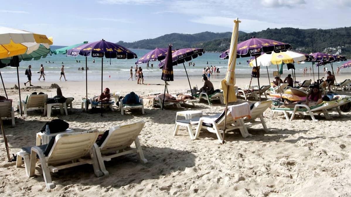 Thaimaalainen ranta on täynnä aurinkotuoleja ja -varjoja.