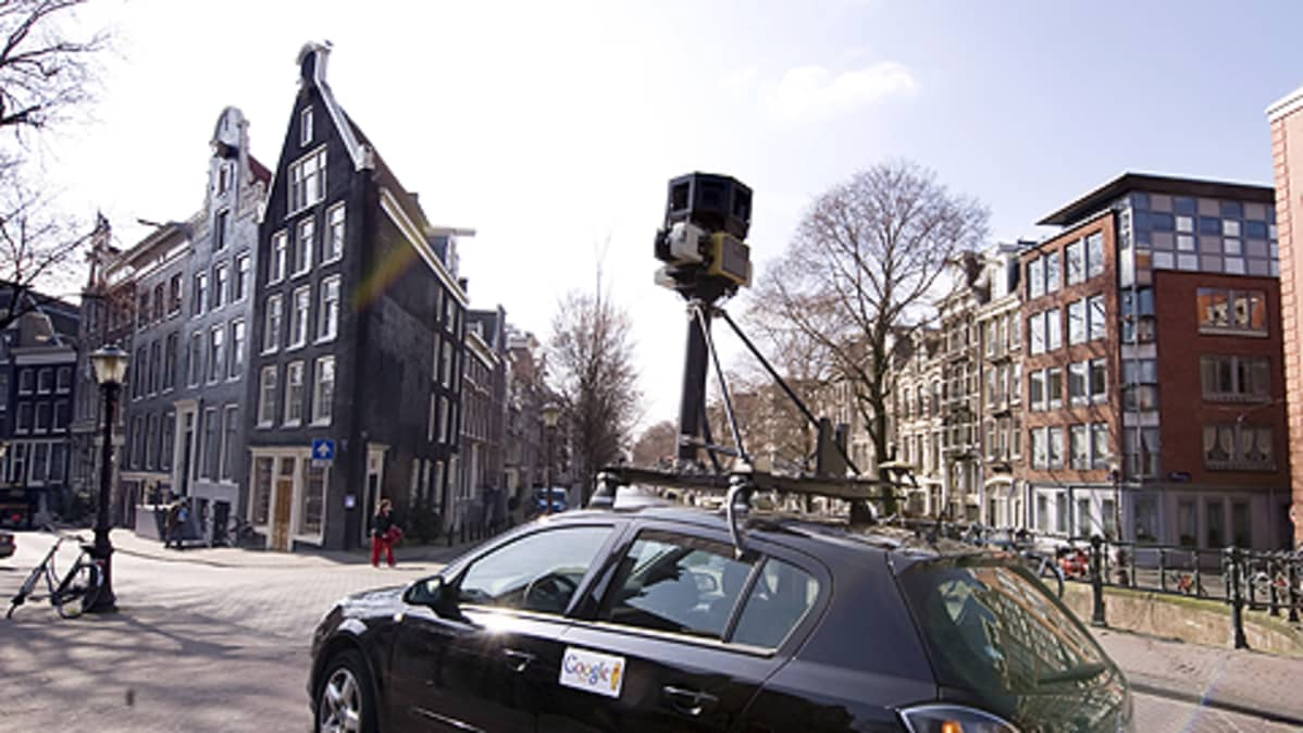 Henkilöauto, jonka katolle noin metrin korkeuteen on asennettu kamera. Auton ovessa Googlen tarra. Aurinkoinen katumaisema Amsterdamissa.