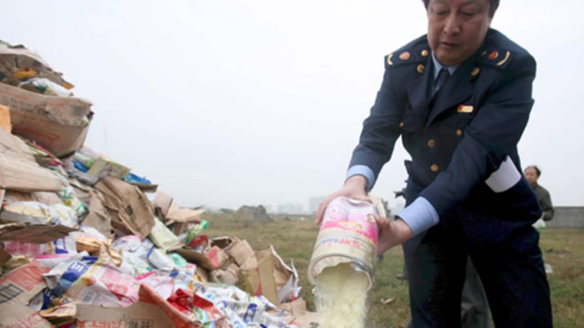 Kiinalaisviranomainen tyhjentää maitojauhepurkkia