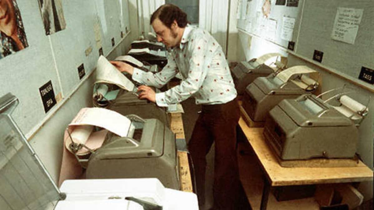 Mies katsoo printterillä tullutta uutistoimistosähkettä