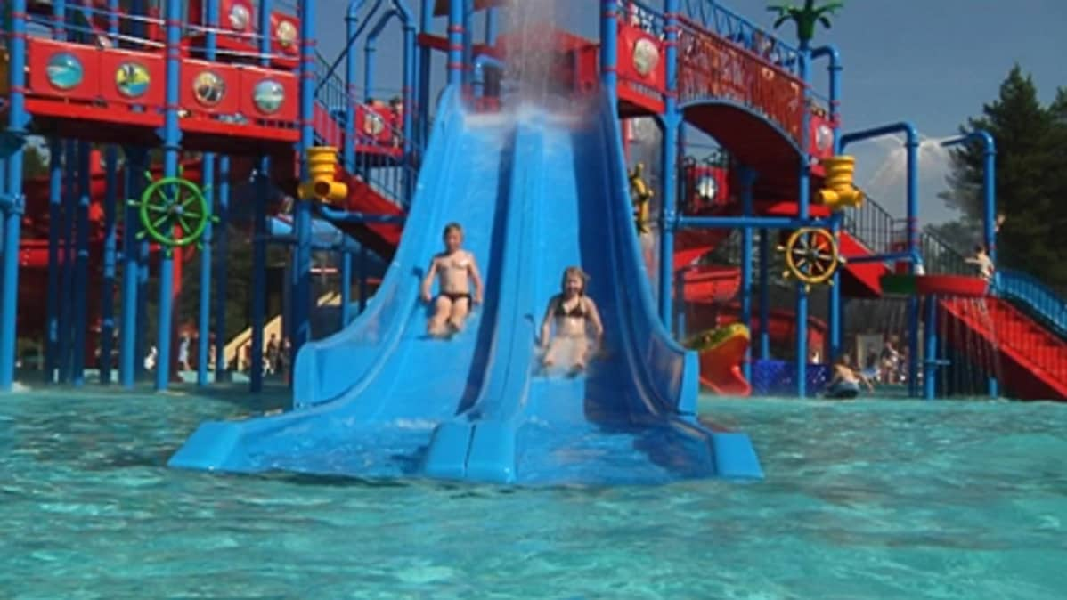 Kaksi lasta laskee Jukuparkin vesiliukumäessä.