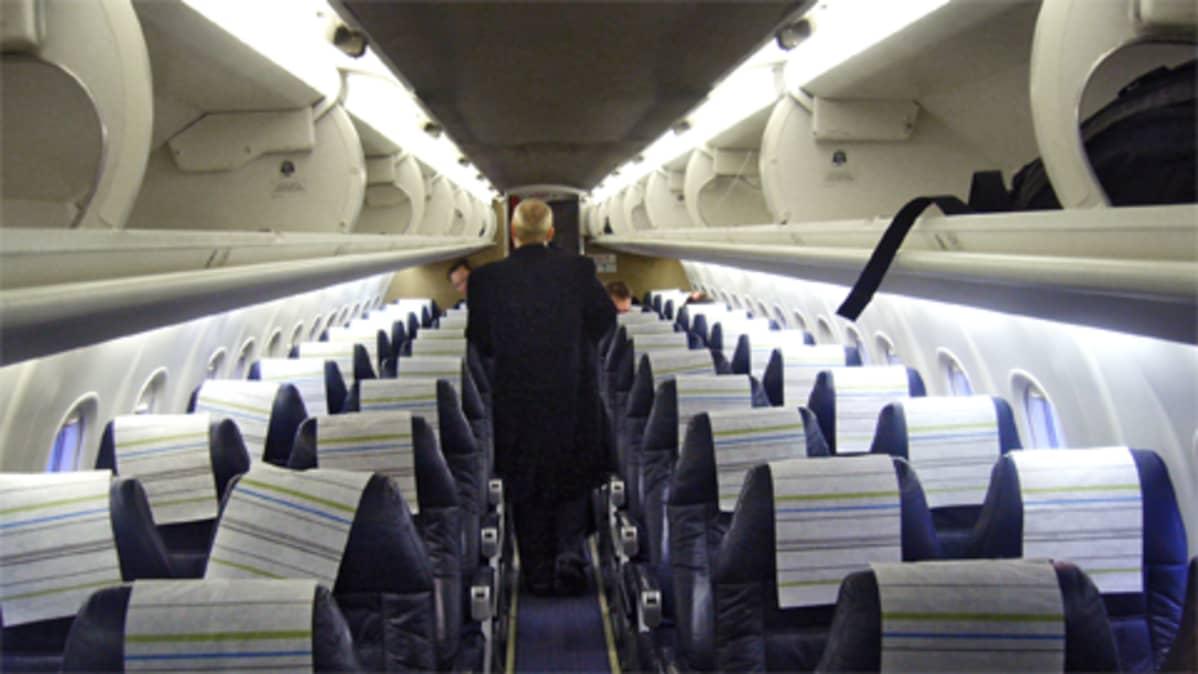 Mies kävelee lentokoneen matkustamon käytävällä.