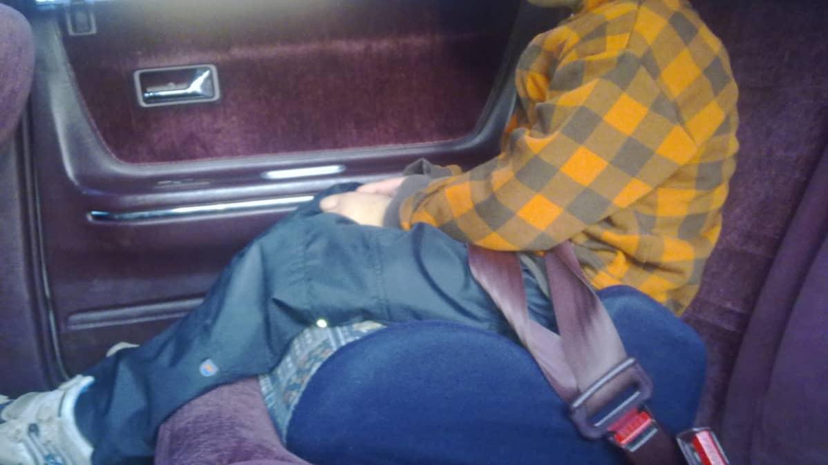 Lapsi istuu auton istuinkorokkeella.