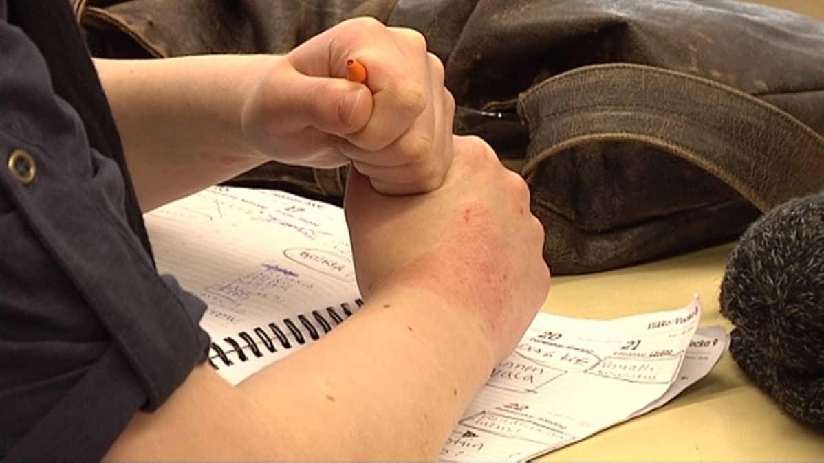 Opiskelija puristaa mustekynää käsissään.