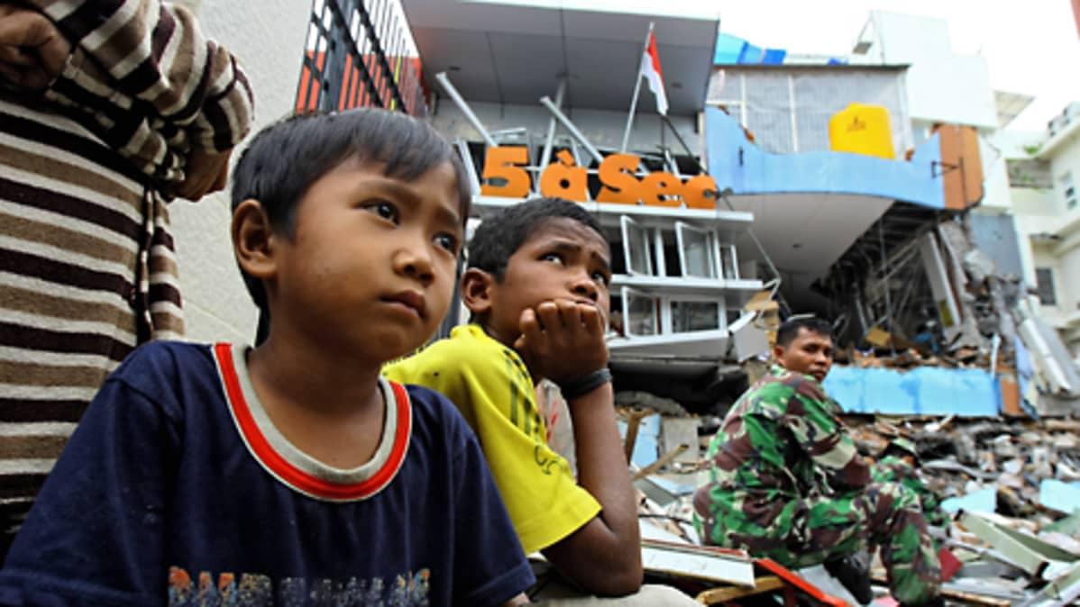 Kaksi lasta istuu tuhoutuneiden rakennusten raunioilla Padangissa, Länsi-Sumatralla. Armeijan sotilas istuu samoilla raunioilla taaempana.