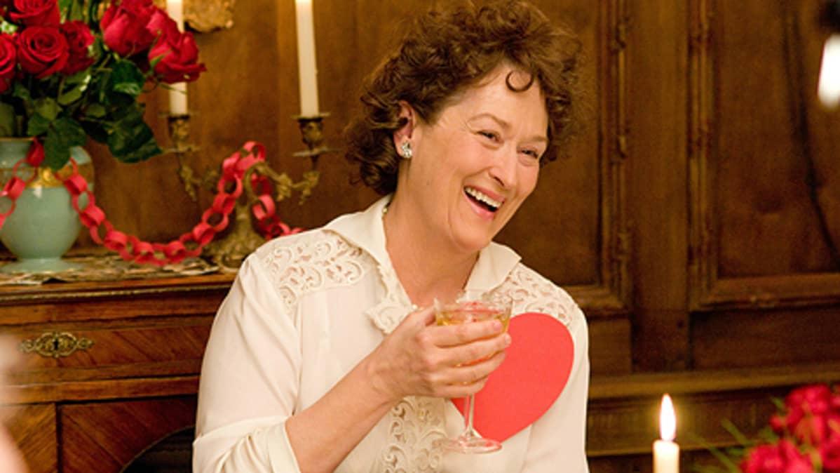 Meryl Streep esittää Julia Childia. Hymyilee viinilasi kädessään.